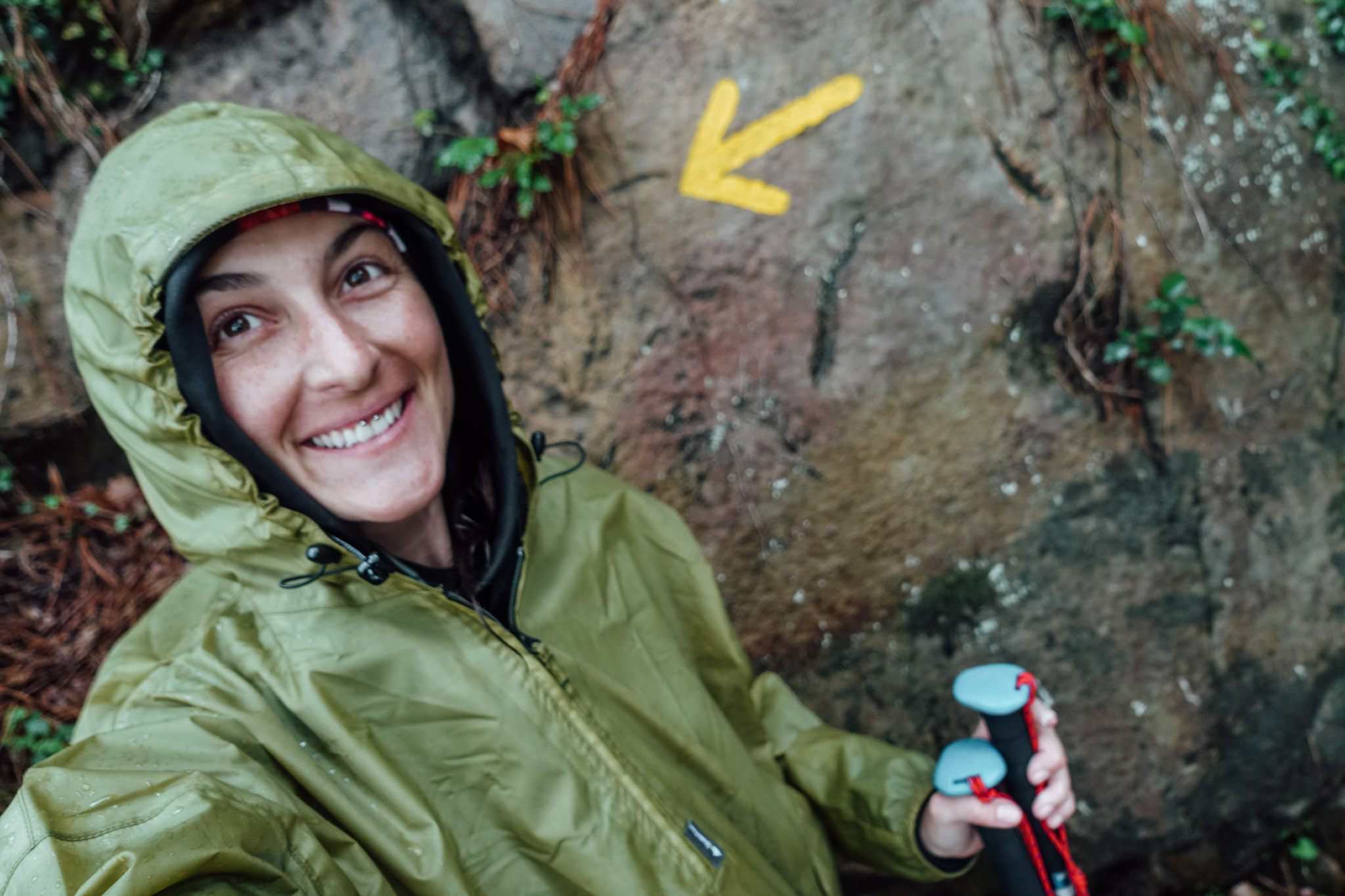 Author, Hayli Nicole, takes a selfie with a yellow arrow on the Camino Del Norte in Spain